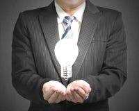 Homme d'affaires d'ouverture de paume avec l'ampoule Images libres de droits