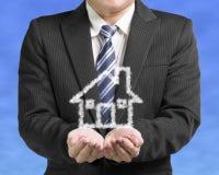 Homme d'affaires d'ouverture de paume avec la maison de forme de nuage au CCB de ciel bleu Photo libre de droits