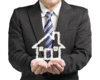 Homme d'affaires d'ouverture de paume avec la maison de forme de nuage dans le backgr blanc Photographie stock libre de droits
