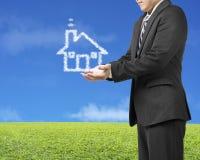 Homme d'affaires d'ouverture de paume avec la maison de forme de nuage dans le pré vert Image libre de droits