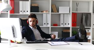 Homme d'affaires dans des écouteurs fonctionnant avec des jambes sur la table banque de vidéos