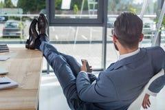 Homme d'affaires dans des écouteurs se reposant au lieu de travail et à la musique de écoute Images stock