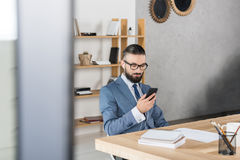Homme d'affaires dans des écouteurs utilisant le smartphone et musique de écoute sur le lieu de travail Image stock