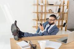 Homme d'affaires dans des écouteurs utilisant le smartphone et musique de écoute sur le lieu de travail Image libre de droits
