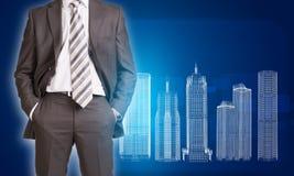 Homme d'affaires dans des bâtiments de costume et de fil-cadre Photo stock