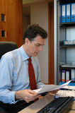 Homme d'affaires dans des documents du relevé de bureau photographie stock