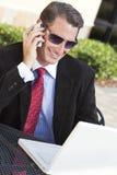 Homme d'affaires dans des lunettes de soleil avec l'ordinateur portatif et le téléphone portable photographie stock