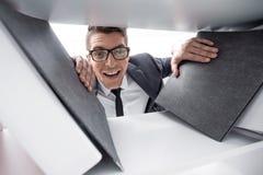 Homme d'affaires dans des sourires et des regards en verre à la caméra photos stock