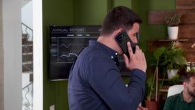 Homme d'affaires dans des vêtements sport ayant une conversation téléphonique importante banque de vidéos