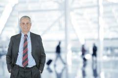 Homme d'affaires dans l'aéroport avec les voyageurs brouillés à l'arrière-plan Image libre de droits