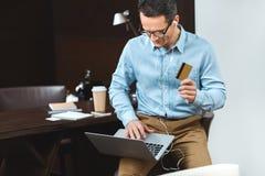 homme d'affaires dans l'habillement de tenue professionnelle décontractée tenant sa carte de crédit tout en à l'aide de l'ordinat Images stock