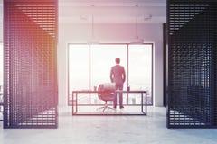 Homme d'affaires dans l'intérieur de bureau du directeur de mur en métal Photo stock