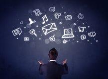 Homme d'affaires dans la chaise avec des icônes de multimédia au-dessus de sa tête Photo libre de droits