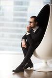 Homme d'affaires dans la chaise d'oeufs pensant à l'avenir Photos libres de droits