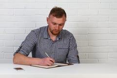 Homme d'affaires dans la lecture occasionnelle de tissu et document de signature dans le bureau Le hippie d'homme d'affaires sign photos stock