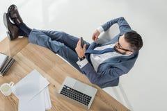 Homme d'affaires dans la musique de écoute d'écouteurs tout en se reposant sur le lieu de travail avec l'ordinateur portable Photographie stock