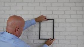 Homme d'affaires dans la position de cadre de photo de découverte de chambre de bureau décorant le mur intérieur banque de vidéos