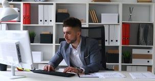 Homme d'affaires dans la veste grise se reposant à la table dans le bureau blanc, imprimant sur le clavier, et papiers de lanceme clips vidéos