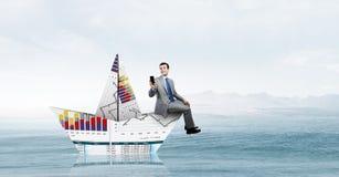 Homme d'affaires dans le bateau fait de papier images stock