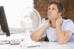 Homme d'affaires dans le bureau avec l'ordinateur et le ventilateur Photos stock