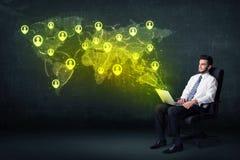 Homme d'affaires dans le bureau avec l'ordinateur portable et la carte sociale du monde de réseau Images libres de droits