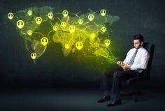 Homme d'affaires dans le bureau avec le comprimé et la carte sociale du monde de réseau Photographie stock