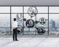 Homme d'affaires dans le bureau regardant aux icônes d'affaires Image stock