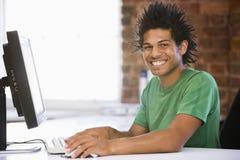 Homme d'affaires dans le bureau tapant sur le sourire d'ordinateur Image libre de droits