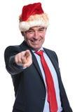 Homme d'affaires dans le chapeau de Noël dirigeant le doigt Photographie stock libre de droits