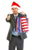 Homme d'affaires dans le chapeau de Santa avec des sacs à provisions Images libres de droits