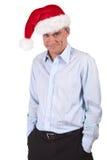 Homme d'affaires dans le chapeau de Santa avec la grimace effrontée Photos stock