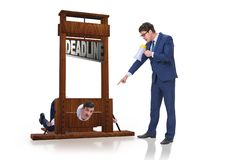 Homme d'affaires dans le concept de date-butoir avec la guillotine photos stock