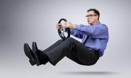 Homme d'affaires dans le conducteur de voiture en verre avec un volant Images stock