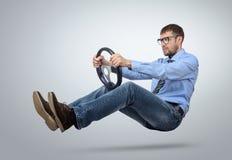 Homme d'affaires dans le conducteur de voiture en verre avec un volant Photos stock