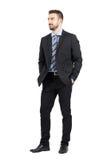 Homme d'affaires dans le costume avec des mains dans des poches souriant et regardant loin Image libre de droits
