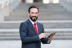 Homme d'affaires dans le costume bleu et le lien rouge travaillant au comprimé numérique devant l'immeuble de bureaux photo stock