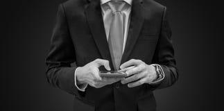 Homme d'affaires dans le costume bleu-foncé utilisant le smartphone mobile, noir et blanc Photographie stock libre de droits