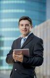 Homme d'affaires dans le costume et cravate tenant le comprimé numérique se tenant dehors travaillant dehors le district des affa Images stock