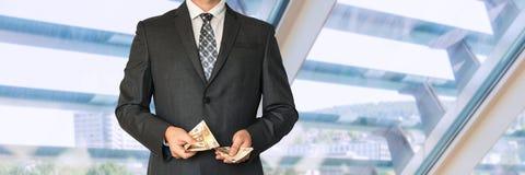 Homme d'affaires dans le costume noir comptant l'argent Photo stock
