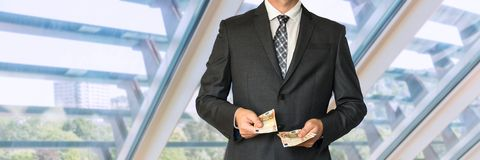 Homme d'affaires dans le costume noir comptant l'argent Images stock