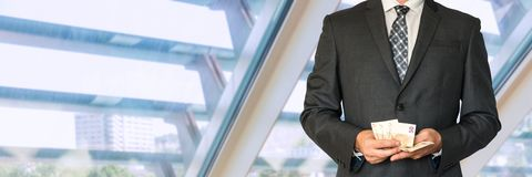Homme d'affaires dans le costume noir comptant l'argent Photos stock