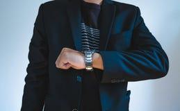 Homme d'affaires dans le costume occasionnel observant une montre Photographie stock