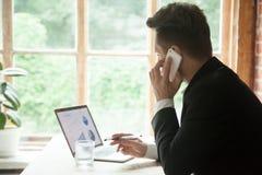 Homme d'affaires dans le costume parlant au téléphone tout en travaillant sur l'ordinateur portable Images stock