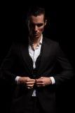 Homme d'affaires dans le costume posant à l'arrière-plan de studio fermant son cric photo stock