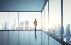 Homme d'affaires dans le costume regardant le lever de soleil dans la ville 3d rendent Photographie stock libre de droits