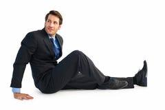 Homme d'affaires dans le costume se reposant sur le plancher images libres de droits