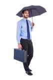 Homme d'affaires dans le costume tenant le parapluie et la serviette Photographie stock
