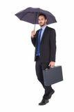 Homme d'affaires dans le costume tenant le parapluie et la serviette Images libres de droits