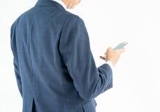 Homme d'affaires dans le costume tenant le smartphone Photographie stock libre de droits