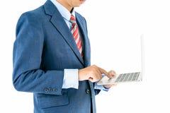 Homme d'affaires dans le costume tenant un ordinateur portable Photographie stock